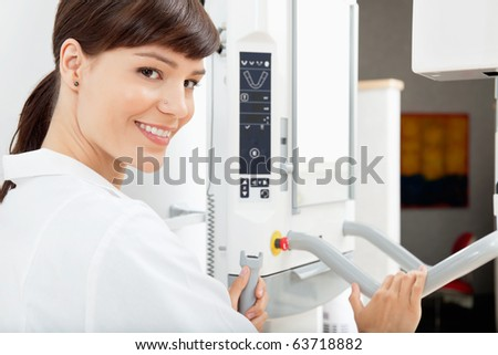 Portrait of a happy female dentist with a  Panoramic Imager X-Ray machine