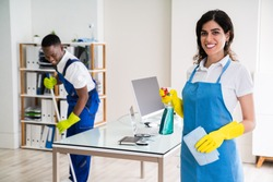 Portrait Of A Happy Female Janitor With Cleaning Equipment In Office