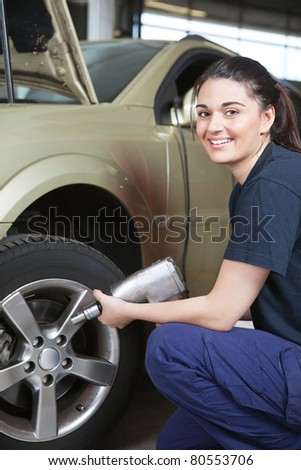 Portrait of a happy female mechanic changing a tire in a shop
