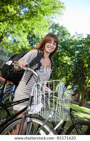 Portrait of a happy female student standing with her bike