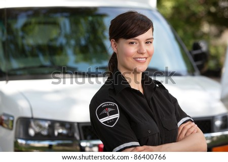 Portrait of a happy friendly female paramedic standing in front of ambulance - stock photo