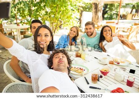 Portrait of a happy friends making selfie photo in outdoor restaurant