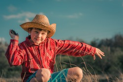Portrait of a happy funny boy, a child in a straw hat. nature is a clear and sunny day. Blue sky in the background