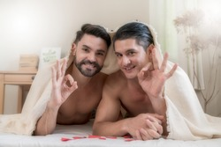 Portrait of a happy gay couple lying under a blanket on the bed together and giving OK sign. Two handsome men lovers relaxing in the bedroom. Concept of LGBTQ+ Life and gender equality. Soft focus