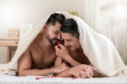 Portrait of a happy gay couple lying under a blanket on the bed together. Two handsome men lovers relaxing in the bedroom. Concept of LGBTQ+ Life and gender equality. Soft focus