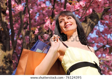 Portrait of a happy girl in a yellow dress walking down the avenue