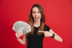 Portrait of a happy girl pointing finger at bunch of money banknotes and winking isolated over pink background