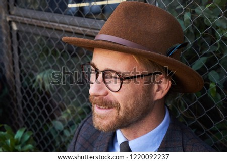 Portrait of a happy handsome bearded male wearing a felt hat and glasses   1220092237 07b28127c1a9