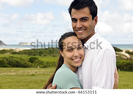 portrait of a happy hispanic couple smiling outdoors
