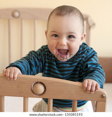 Portrait of  a happy laughing baby standing in a cot.