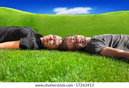 Portrait of a happy laughing couple lying on the grass
