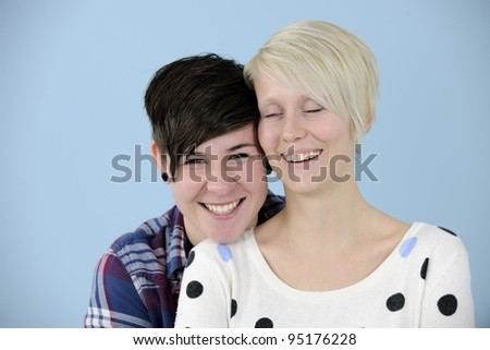 portrait of a happy lesbian couple on blue background