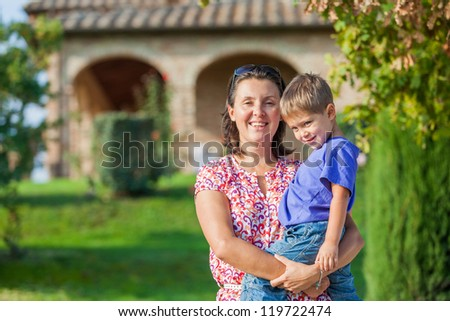 Portrait of a happy little boy with his mother in the garden