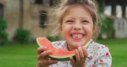 Portrait of a happy little girl is eating a fresh biologic just harvested watermelon and smiling in camera on a background of a countryside farm.