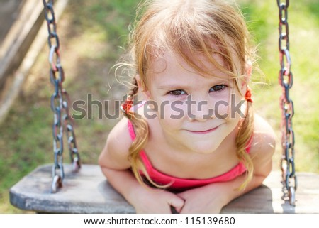 portrait of a happy little girl on a swing