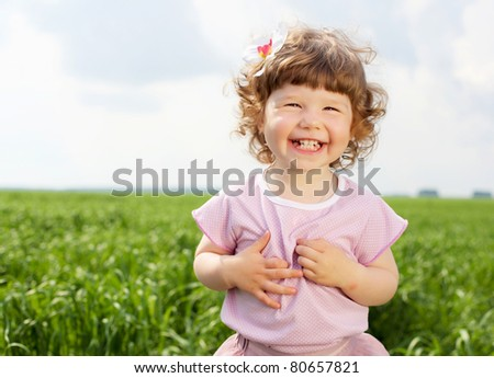 Portrait of a happy little girl outdoors in summer