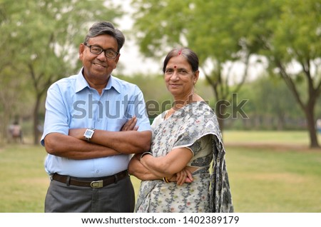 Portrait of a happy looking retired senior Indian man and woman power couple smiling and posing with hands crossed / folded in a park outdoor during spring/summer season in Delhi, India. Concept love