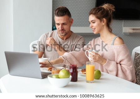 Portrait of a happy loving couple having breakfast while sitting at the table in a kitchen at home and pointing at laptop computer #1008963625