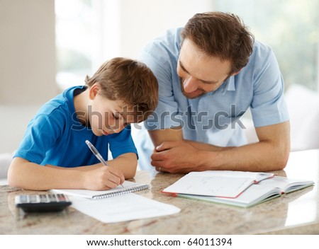 Portrait of a happy man helping his son to do homework Indoor