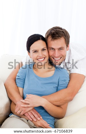 Portrait of a happy man hugging his girlfriend while relaxing on the sofa at home