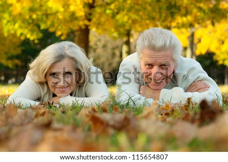 portrait of a happy mature couple lying on the autumn leaves