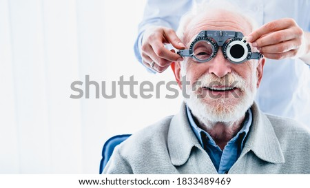Portrait of a happy mature male patient undergoing vision check with special ophthalmic glasses