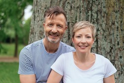 Portrait of a happy middle-age couple looking at camera while posing outdoors in the park