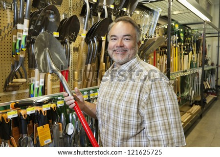Portrait of a happy middle-aged man holding shovel in hardware store