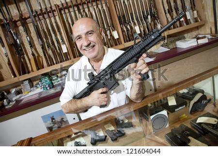 Portrait of a happy middle-aged merchant with rifle in gun shop - stock photo