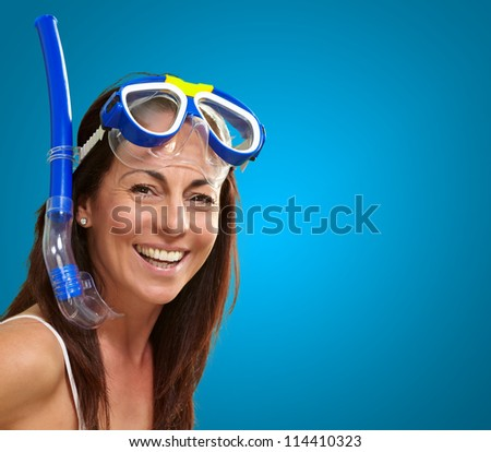 portrait of a happy middle aged woman wearing snorkel and goggles over blue