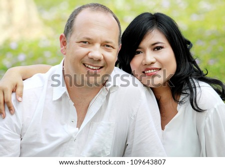 Portrait of a happy mixed race couple outside in the park
