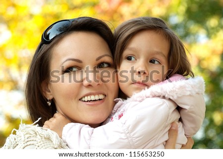 portrait of a happy mom and a little girl in the autumn