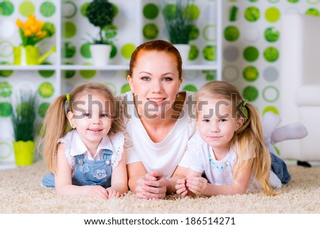 Portrait of a happy mother and her daughters lying on a floor in bright green living room