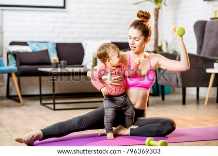 Portrait of a happy mother with her baby son exercising with dumbbells at home #796369303