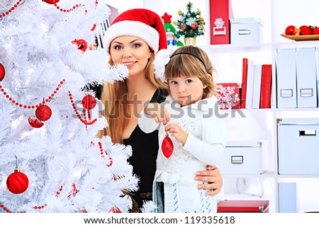 Portrait of a happy mother with her daughter decorating Christmas tree at home.