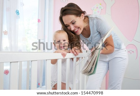 Portrait of a happy mother with smiling baby together in bedroom  - stock photo