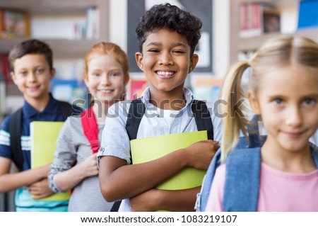 Portrait of a happy multiethnic children holding books and wearing backpack at primary school. Schoolboys and cute girls in a row holding notebook and looking at camera. Elementary child smiling. #1083219107