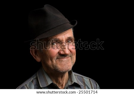 Portrait of a happy old man with hat, isolated on black - stock photo