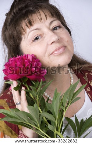 Portrait of a happy old woman with peony