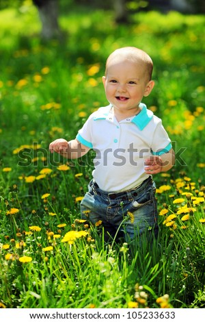 Portrait of a happy one-year old boy on a walk in a park