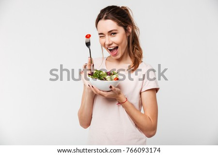 Portrait of a happy playful girl eating fresh salad from a bowl and winking isolated over white background #766093174