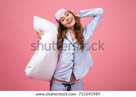 Portrait of a happy pretty girl dressed in pajamas holding pillow and  looking at camera isolated d6fd42d10