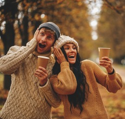 Portrait of a happy romantic couple with coffee walking outdoors. Couple in love. Coffee cups. Life.