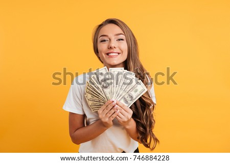 Portrait of a happy satisfied girl holding bunch of money banknotes and looking at camera isolated over yellow background