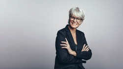 Portrait of a happy senior businesswoman looking at camera. Senior woman entrepreneur with her arms crossed standing against grey background.