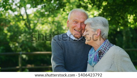 Portrait of a happy senior couple are hugging  with affection as a sign of their forever love and respect to each other in a green park in a sunny day.