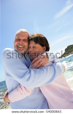 Portrait of a happy senior couple embracing on the beach