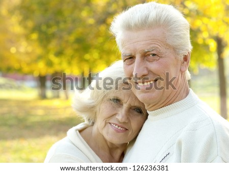 portrait of a happy senior couple standing in autumn park