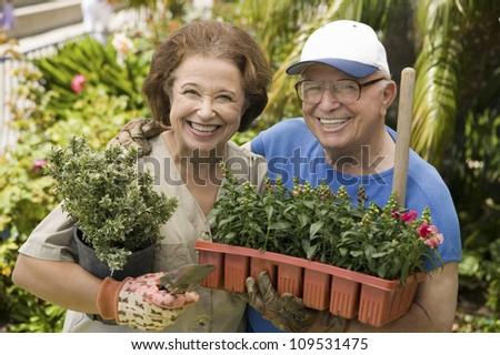 Portrait of a happy senior couple working in their own garden