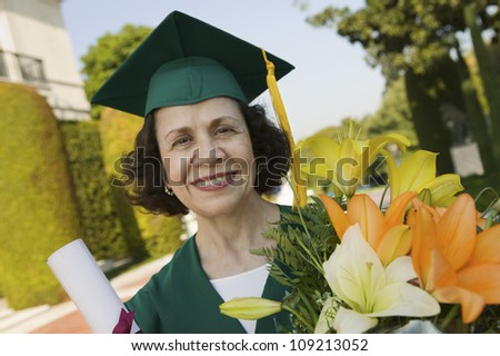 Portrait of a happy senior female graduate holding degree and bouquet